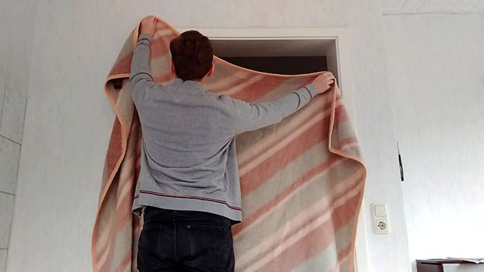 add a wool blanket to keep heat in a room without a door